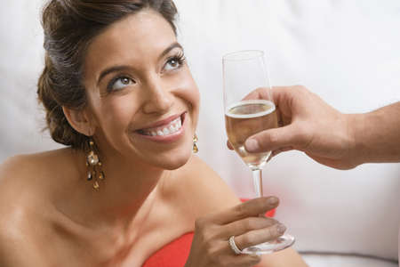 Hispanic woman accepting glass of champagne