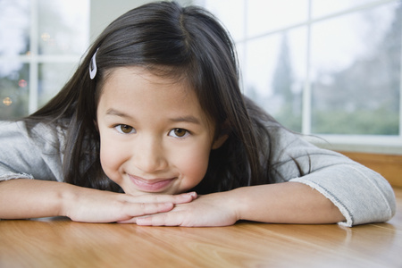 Mixed Race girl resting chin on hands