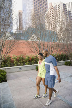 African couple walking on urban sidewalk