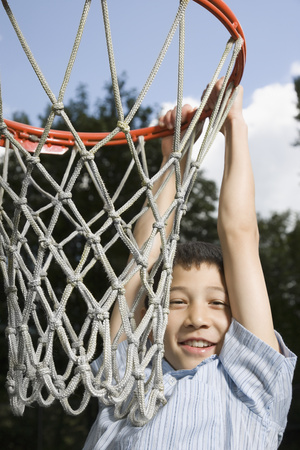 Asian boy hanging from basketball hoop LANG_EVOIMAGES