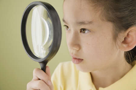 Asian girl looking through magnifying glass