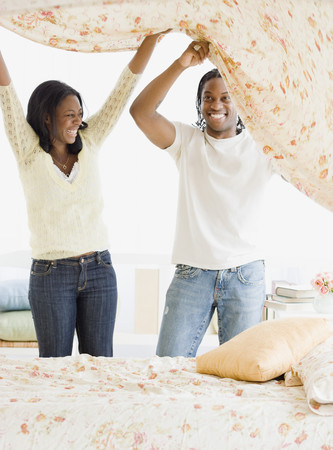 African couple making bed LANG_EVOIMAGES