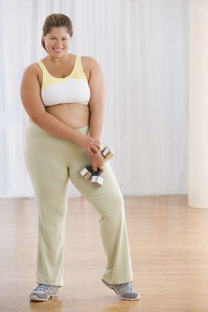 Overweight Hispanic woman holding dumbbells