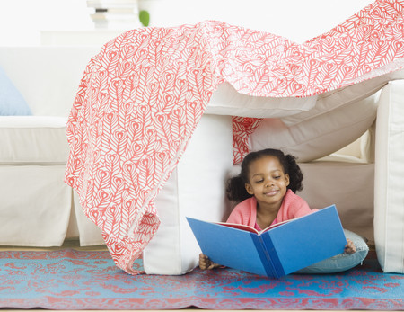 Mixed race girl reading in living room fort