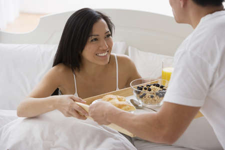 Asian man bringing girlfriend breakfast in bed