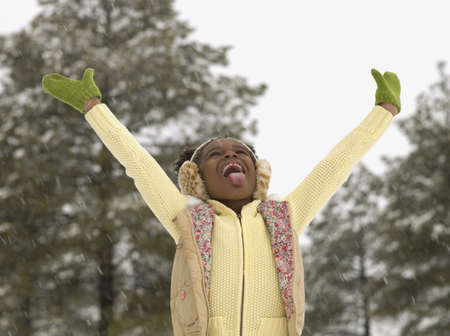 African girl catching snowflakes on her tongue LANG_EVOIMAGES