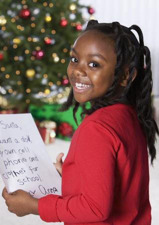 African girl holding letter for Santa Claus