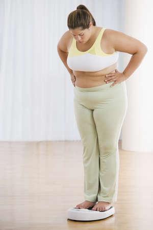 Overweight Hispanic woman on scale