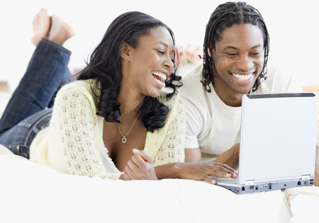 African couple on laptop in bed LANG_EVOIMAGES