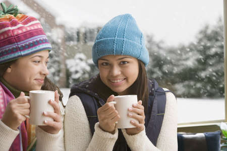 Multi-ethnic girls in snow drinking hot cocoa LANG_EVOIMAGES