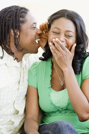 African man whispering in womans ear