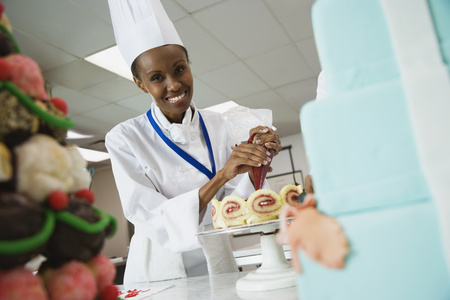 African female pastry chef decorating cake