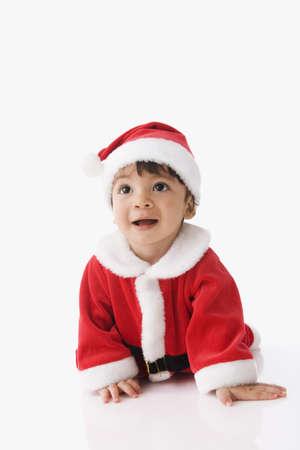 Hispanic baby wearing Santa Claus suit LANG_EVOIMAGES