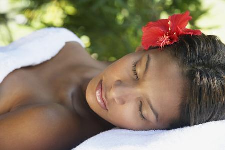 Hispanic woman laying on spa table LANG_EVOIMAGES