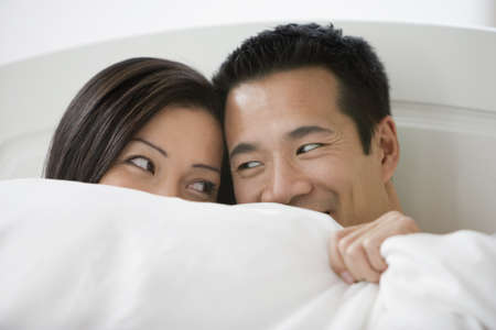 Asian couple smiling at each other in bed LANG_EVOIMAGES