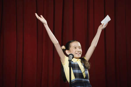 Asian girl with arms raised on stage LANG_EVOIMAGES
