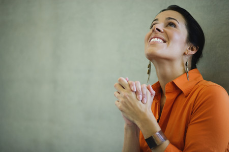 Latin American businesswoman with hands clasped looking hopeful