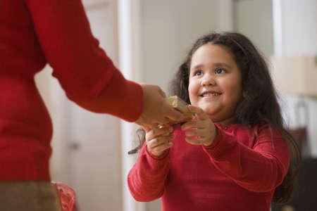 Hispanic girl receiving Christmas gift LANG_EVOIMAGES