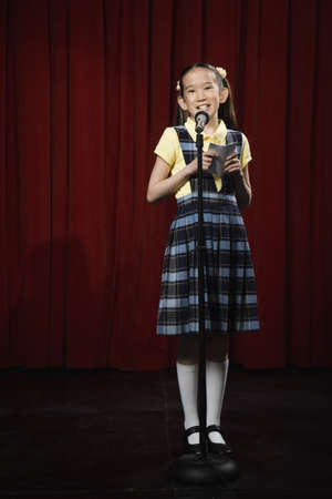 Asian girl speaking into microphone on stage LANG_EVOIMAGES