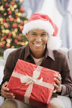 Mixed Race man holding Christmas gift LANG_EVOIMAGES