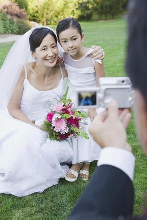 Asian bride and flower girl having photograph taken LANG_EVOIMAGES