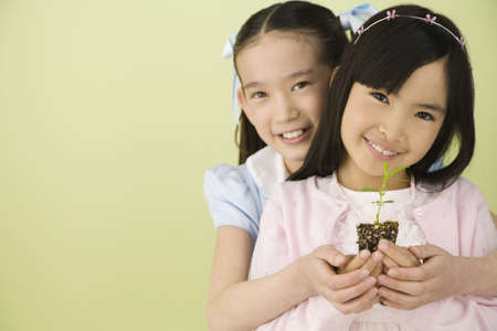 Asian sisters holding new plant