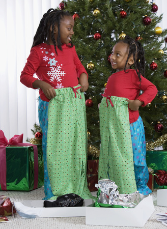 African sisters holding matching Christmas gifts LANG_EVOIMAGES