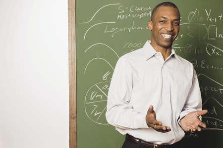 Male mixed race teacher in front of blackboard
