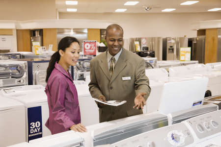 Salesman helping customer in appliance showroom LANG_EVOIMAGES
