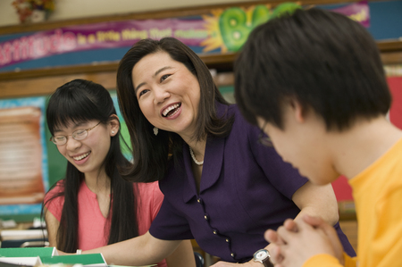 Asian school teacher laughing with students