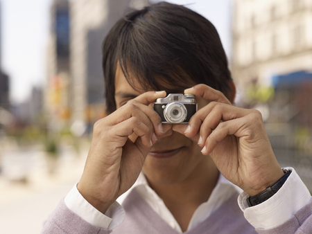 Indian man taking photograph with miniature camera