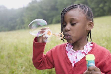 African girl blowing bubbles in field