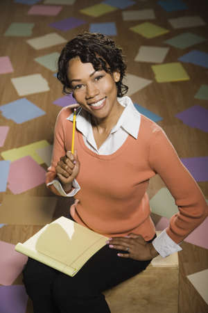 Confident mixed race businesswoman sitting with notepad