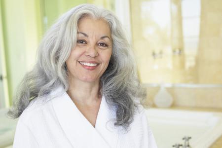 Smiling woman wearing bathrobe in spa