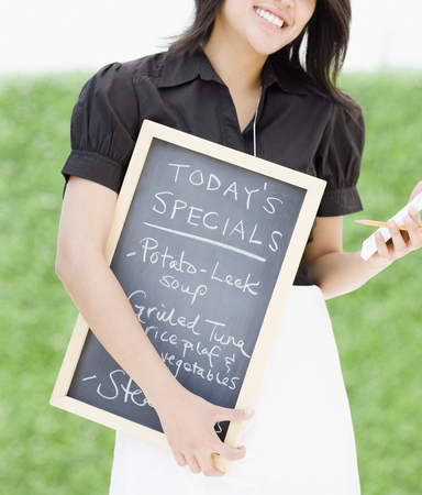 Asian waitress holding chalkboard with day's specials LANG_EVOIMAGES