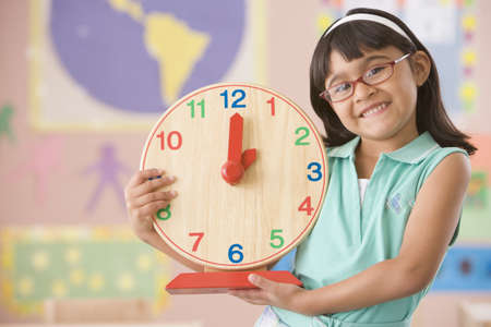 Hispanic school girl holding clock
