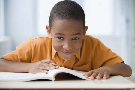 Grinning African boy doing homework