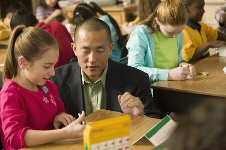 Asian school teacher helping students