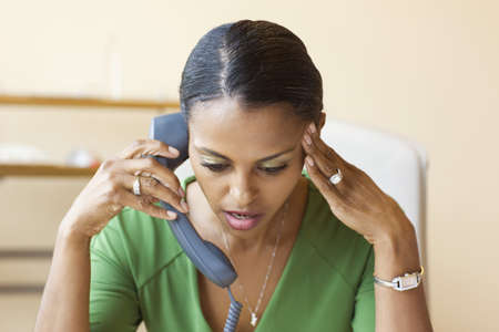 Frustrated African businesswoman talking on telephone