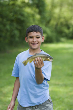 Mixed race boy holding fish he caught