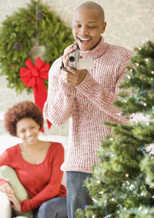 African man using video camera to film Christmas tree