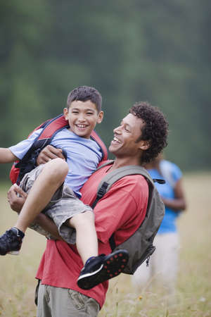 Mixed race father lifting son