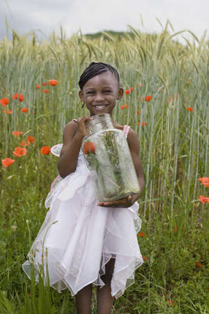 African girl holding insect jar LANG_EVOIMAGES