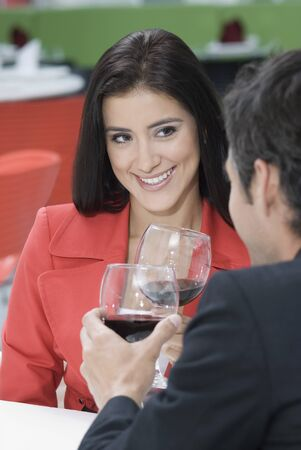 Hispanic couple on date drinking wine