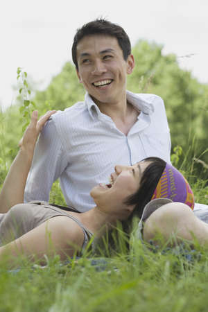 Asian couple laughing in park