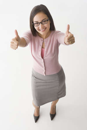 Mixed race businesswoman giving thumbs up