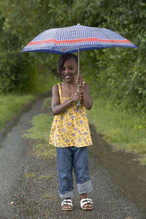 African girl holding umbrella in rain