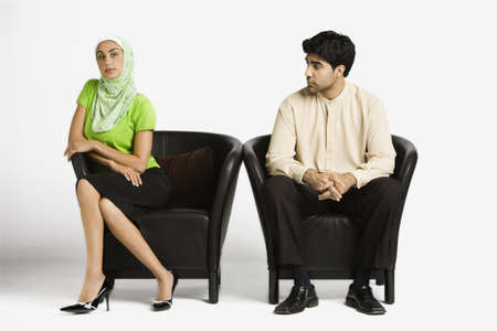 Middle Eastern man and woman sitting in chairs