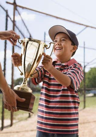 Mixed race boy holding baseball trophy