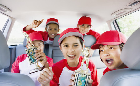 Multi-ethnic boys in car wearing baseball uniforms and holding trophies LANG_EVOIMAGES